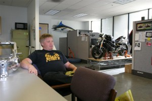 Christian kicking back at the SpeedyMoto office.  That's their Ducati Monster development bike in the background and to the left is a custom 250 MotoGP frame on the conference table.